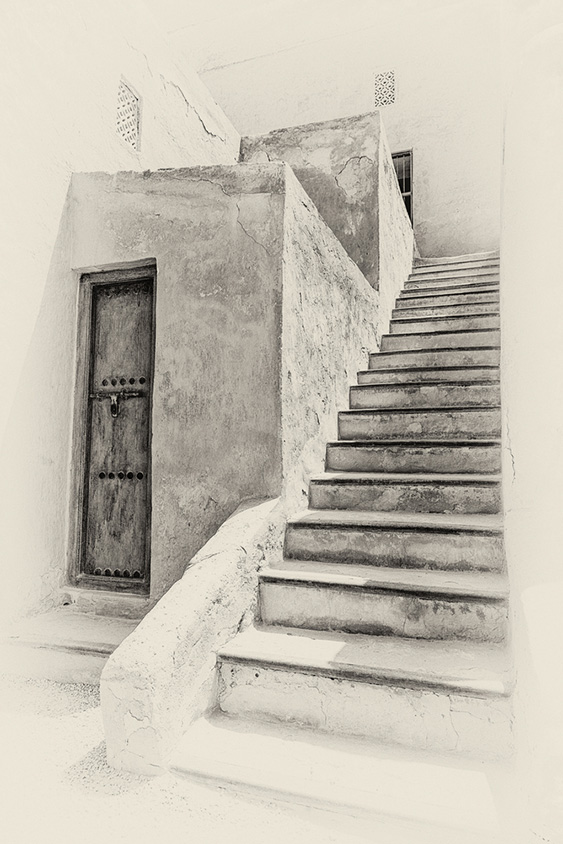 A sepia view of a stairway leading to an upper story