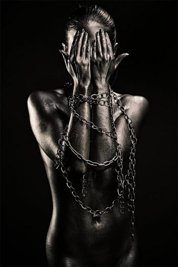 Nude silver woman with hands in chains