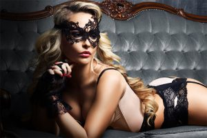 young woman posing in sexy lingerie and Venetian mask