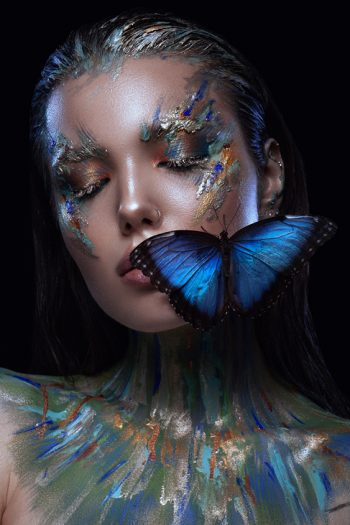 girl with creative makeup and blue butterfly
