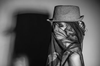 female model with hat and veil on the face