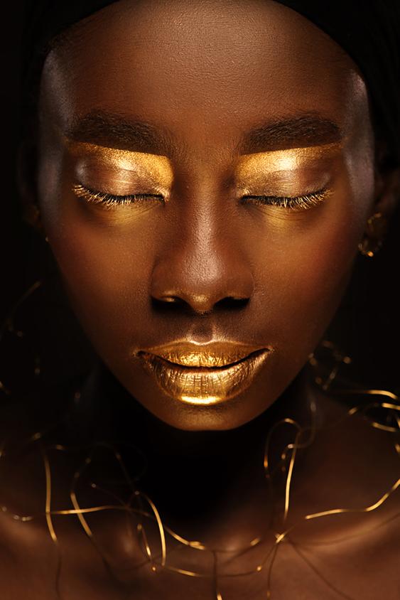 Afrikaanse vrouw met creatieve gouden make-up