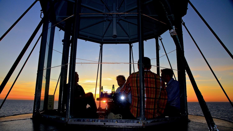 Gäster sitter uppe i lanterninen under solnedgången.