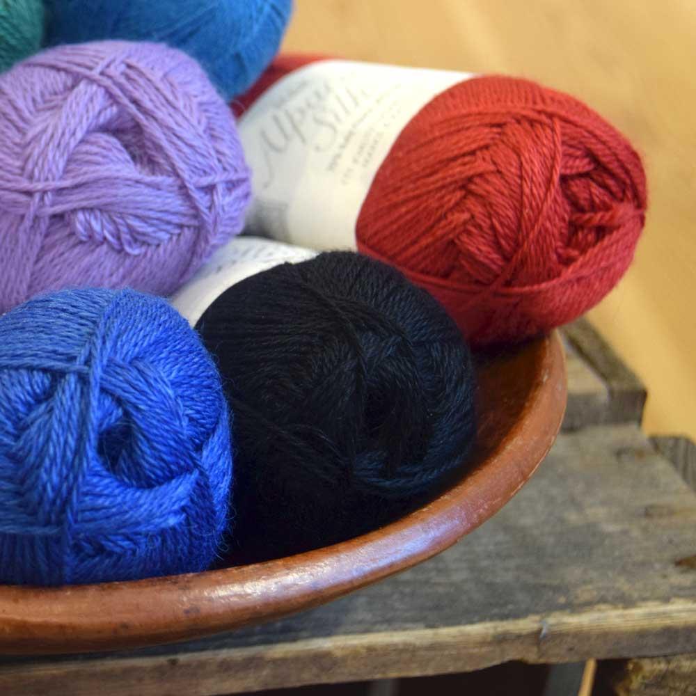 Det bløde Alpaca Silk-garn, som her ses i rød, lilla, blå og sort