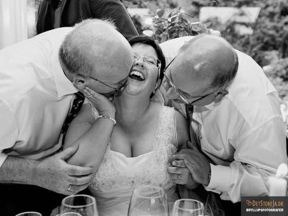 fotograf til festen brud kysses af to gæster