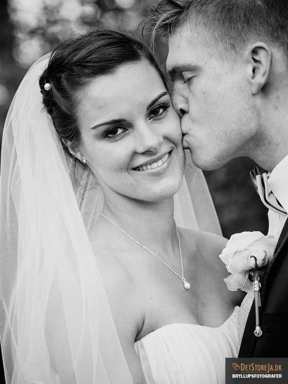 bryllupsfotografering bryllupsbillede brud kysses på kinden af gom