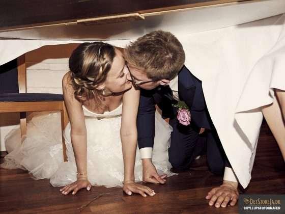 fotograf til festen brudepar kysser under bordet