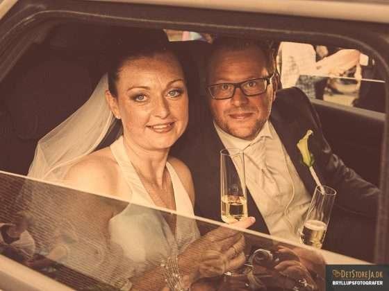 bryllup fotograf brudepar med champagne smiler til fotografen