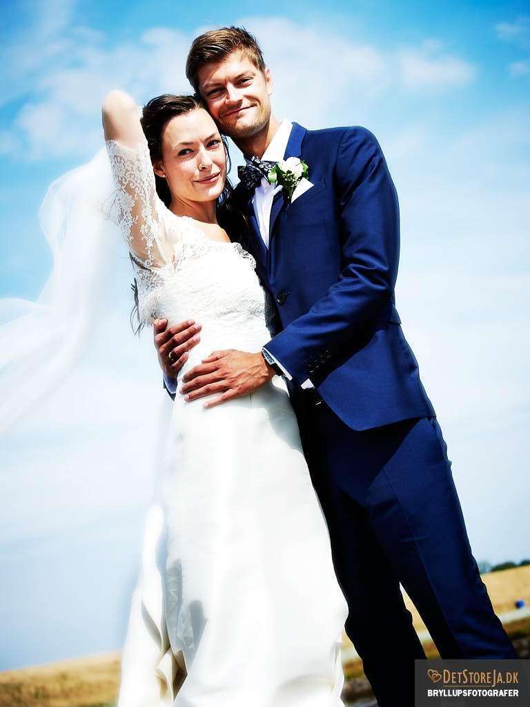 bryllupsfotografer brudepar nedefra blå himmel blæst