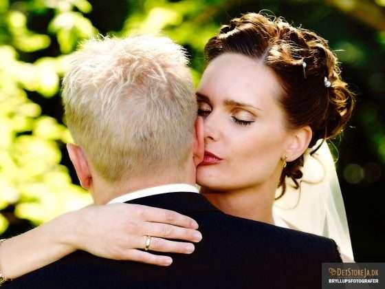 bryllupsfotograf smuk brud kysser sin goms øreflip