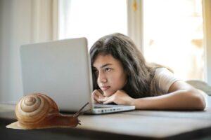 kvinde venter på langsom hjemmeside ved laptop og snegl dinkum.dk