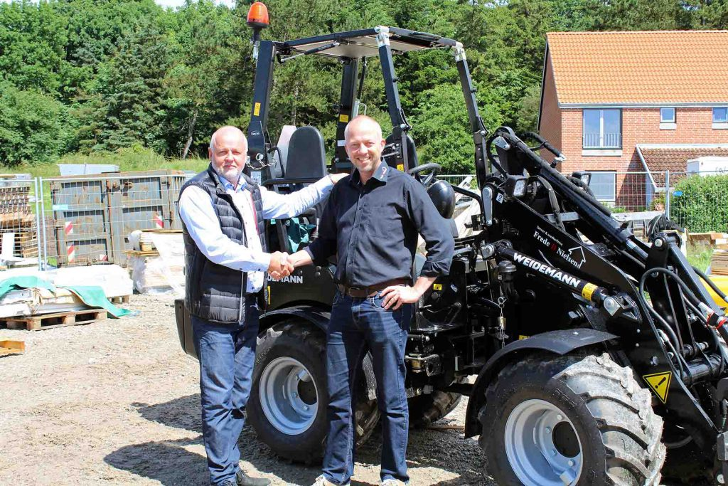 Stemas har leveret den nye Weidemann 1350 CX45 til Tømrer- og Snedkerfirmaet Frede D. Nielsen. Salgschef Robert Kjærgaard (til venstre) og tømrermester Peter Berg-Mortensen giver hånd på handelen med den sorte maskine.