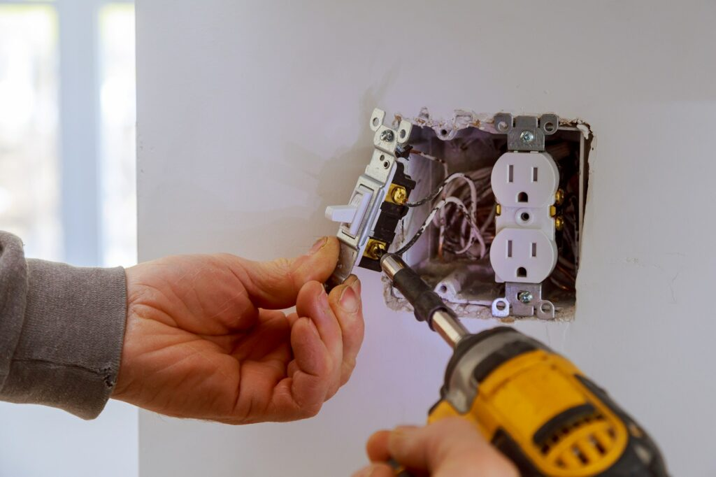 The hands of an electrician installing a power switch to the electrical junction box