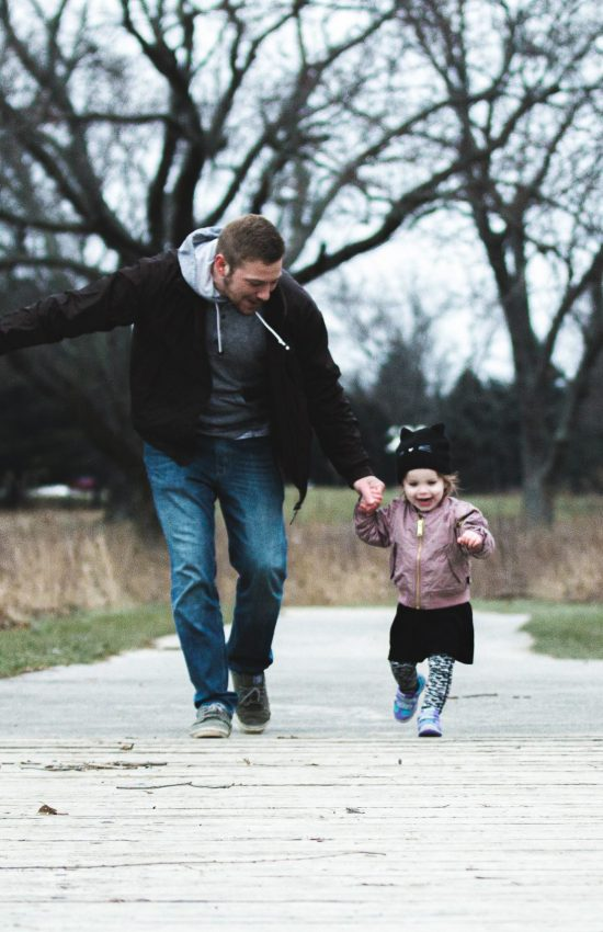 photo-of-father-and-daughter-running-at-the-park-853408