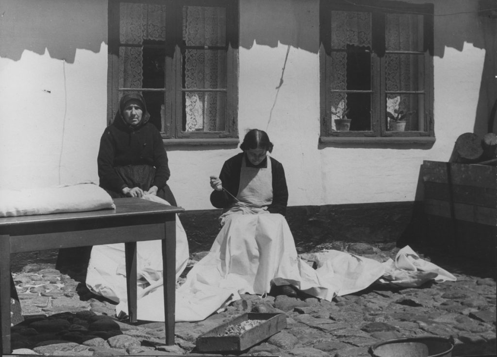 Nelly Jansen (siddende) syr stropper i klæde, før det kan lægges ud til blegning på strandengen. Foto i Dansk Folkemuseum, 1935.