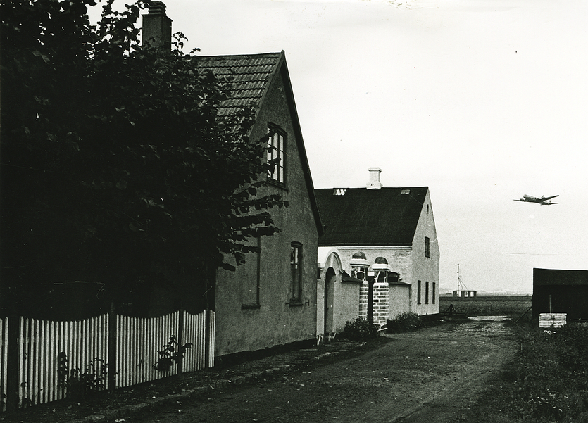 Hjørnegård med et fly i baggrunden. 1971. Foto: Vagn Jacobsen.