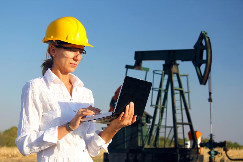 Vrouwelijke ingenieur die op een notebook werkt in een olieveld