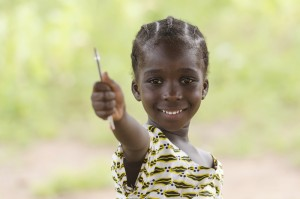 Education symbol: little African black teenage girl holding pen in the air lightly smiling to the camera. African children need education since it is the most important thing for a better future.
