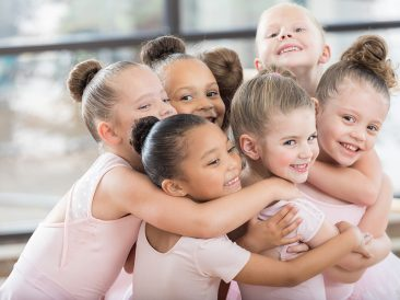 A group of young smiling ballerinas hug each other in a large huddle.  Three of them are looking at the camera.