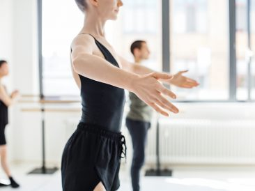 Midsection of ballet dancer rehearsing at studio. Side view of young female are practicing on dance floor. She is wearing sportswear.