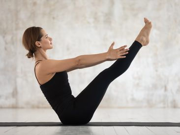 Sporty woman practicing yoga, doing Paripurna Navasana exercise, balance pose, weight loss, attractive sporty girl wearing black sportswear working out at home or in yoga studio with grey walls