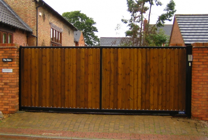 Wooden sliding gate designed to look like twin swing gates