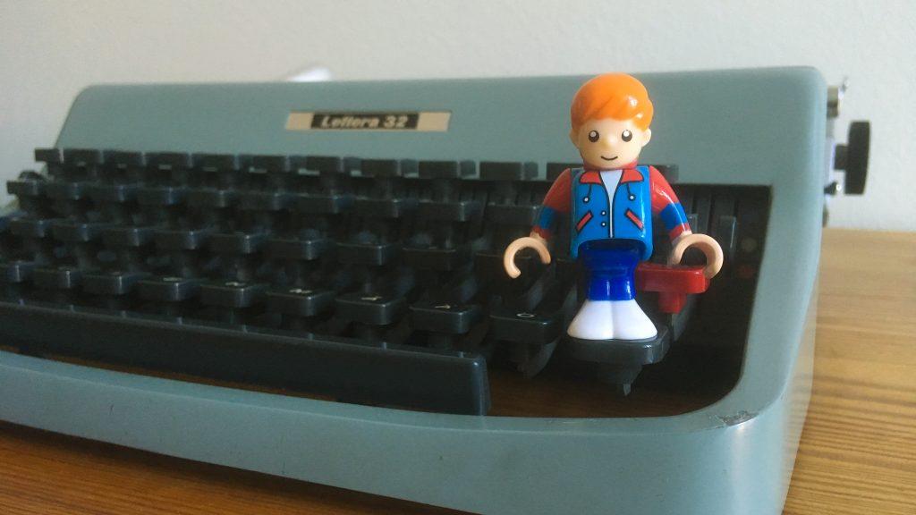 En Brio-docka står vänd mot betraktaren på en av tangenterna till en skrivmaskin Lettera 32.