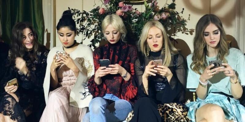 delle influencer guardano il telefono durante una sfilata