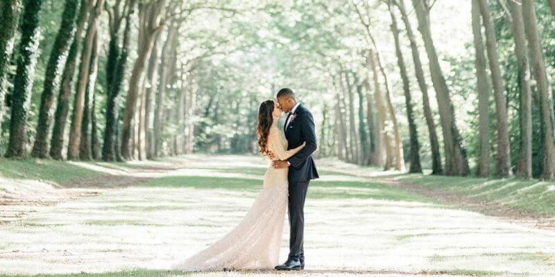 una coppia si bacia sotto gli alberi nelle foto di nozze