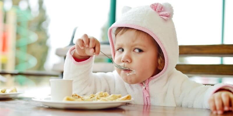 una bambina con una felpa da orsetto mangia la colazione