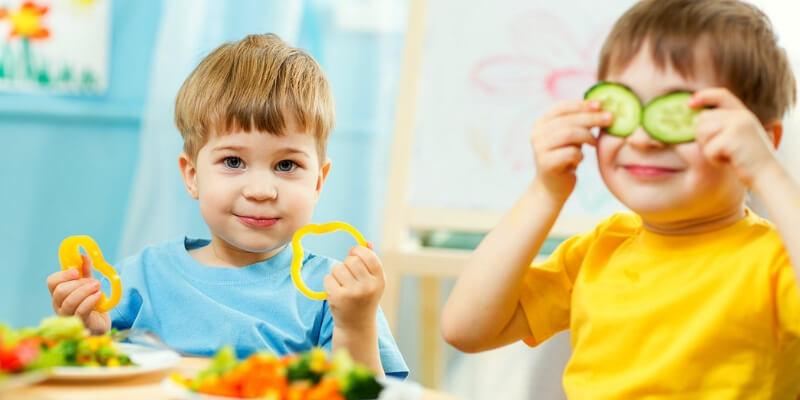 due bambini giocano con delle verdure