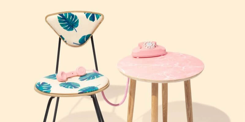 un telefono rosa vicino a una sedia retro con stampa a foglie di palma