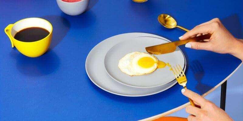 close up di un piatto con uovo fritto su tavolo blu
