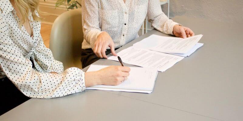 close up sulle mani di due donne alla scrivania
