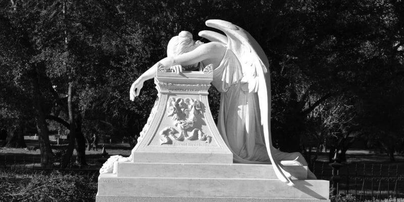 una scultura tombale con un angelo che piange