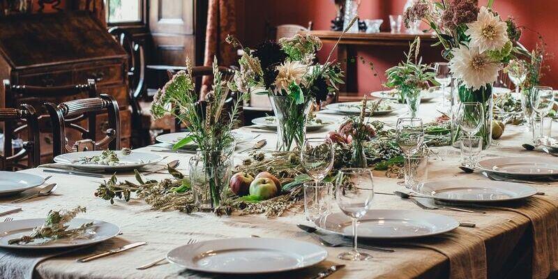un grande tavolo imbandito e decorato da mele