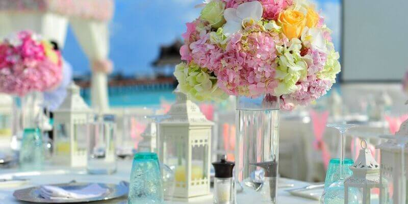 una tavola imbandita con dei fiori color pastello alle maldive
