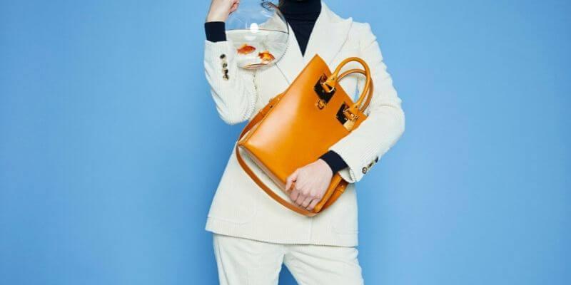 una modella con una borsa e una boccia di pesci rossi
