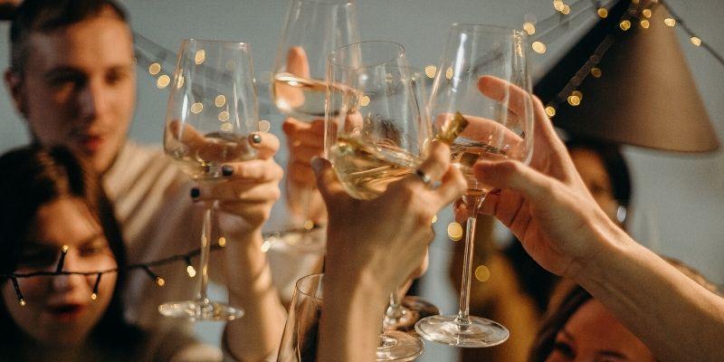un gruppo di persona brinda con dei calici di vino bianco