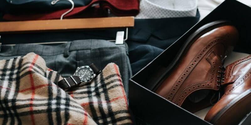 una sciarpa, un orologio e un completo e delle scarpe su un letto, come se si dovesse preparare una valigia