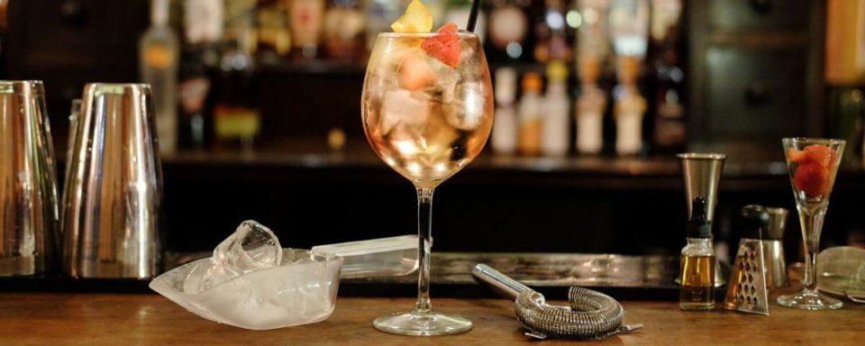 un bicchiere con un cocktail appoggiatosul bancone del bar