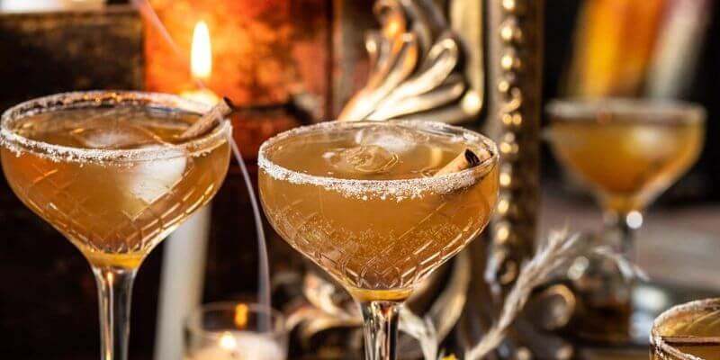 Due cocktail con delle candele sullo sfondo