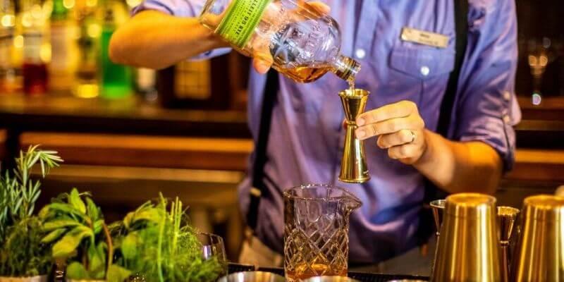 un barman misura gli ingredienti per un cocktail