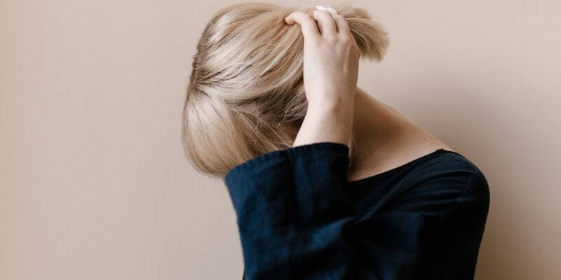 una ragazza nasconde il volto con un braccio