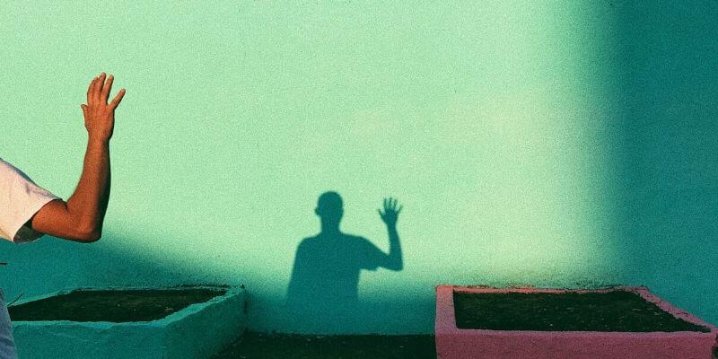 un ragazzo con il braccio alzato in saluto proietta la sua ombra su un muro verde