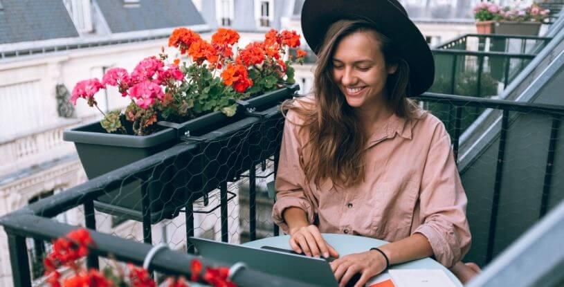 una ragazza al computer sul balcone di casa