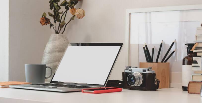 una scrivania con un computer e una macchina fotografica