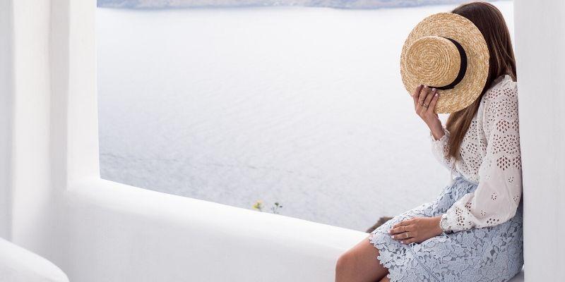una ragazza che si copre il viso con un cappello di paglia
