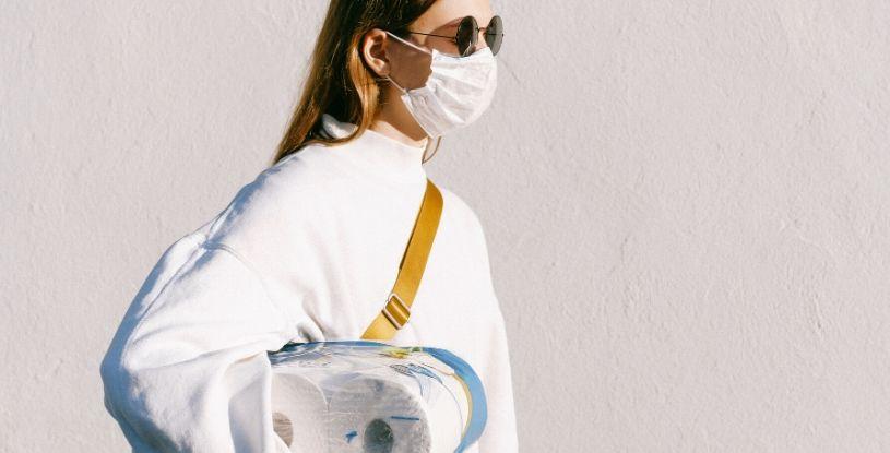 una ragazza con la mascherina e della carta igienica sotto il braccio