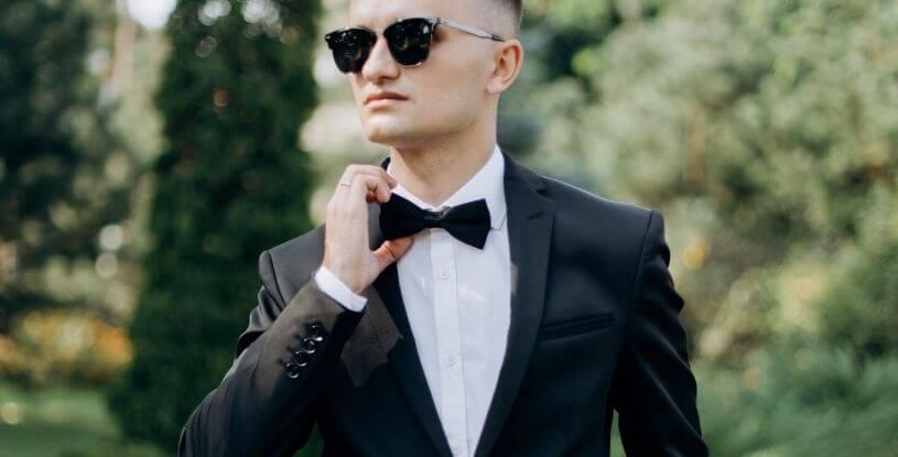 un ragazzo con lo smoking e gli occhiali da sole